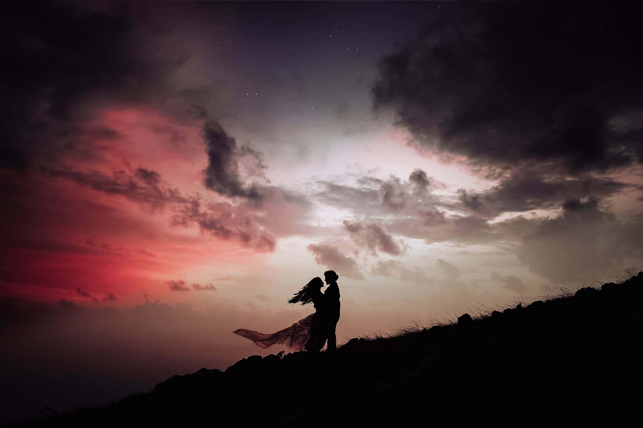 A beautiful photo of two lovers standing on a hill in front of the night sky