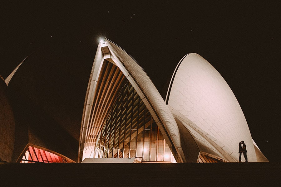 A man and a woman kissing in front of the Sydney Opera house at night