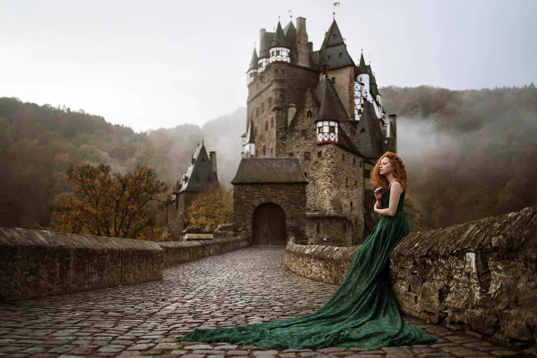 A girl in green clothes is waiting on a bridge which leads to a castle