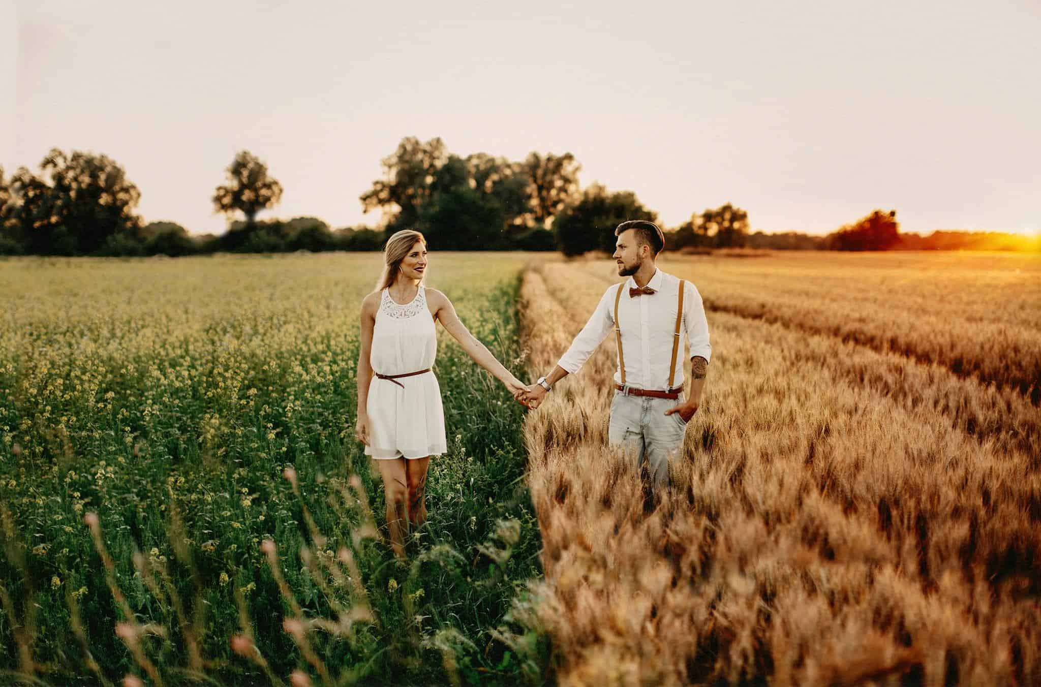 A man and a woman standing in a field holding hands
