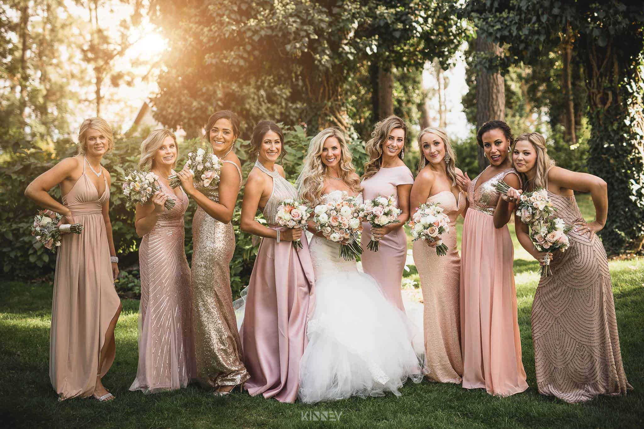 Eight women who are wearing matching colored outfits and a bride are standing on grass