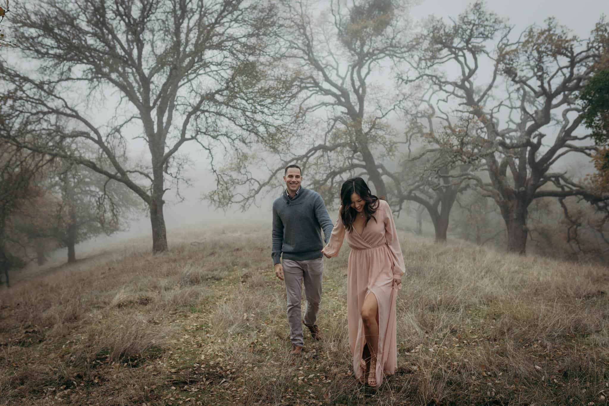 A couple walking in a foggy field surrounded by trees