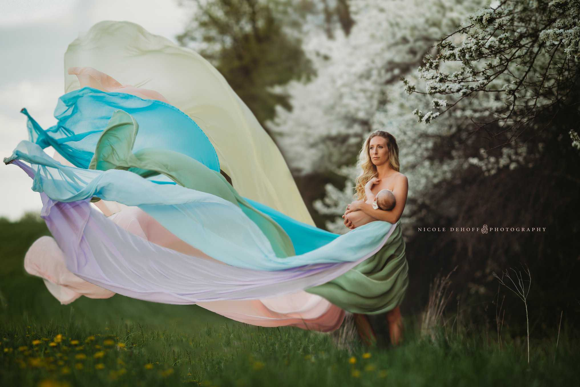 A woman breastfeeding her baby while her dress is flowing in the wind