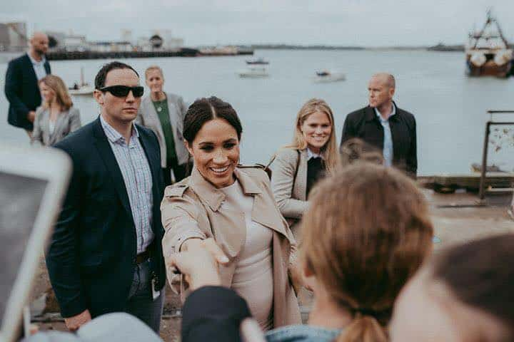 Meghan Markle is shaking hands with a person waiting for her at the pier