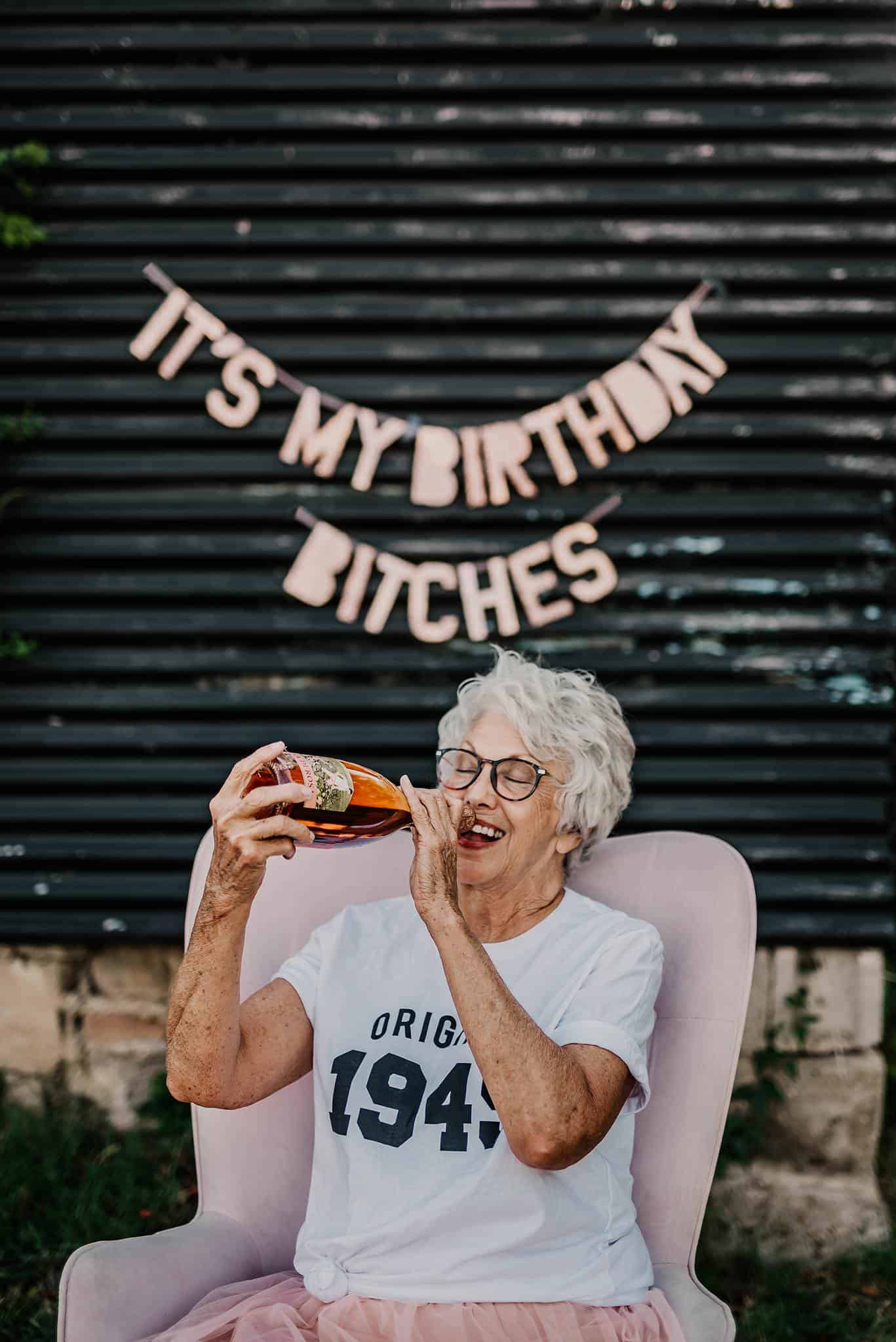 An old grandma is celebrating her birthday by drinking some alcohol