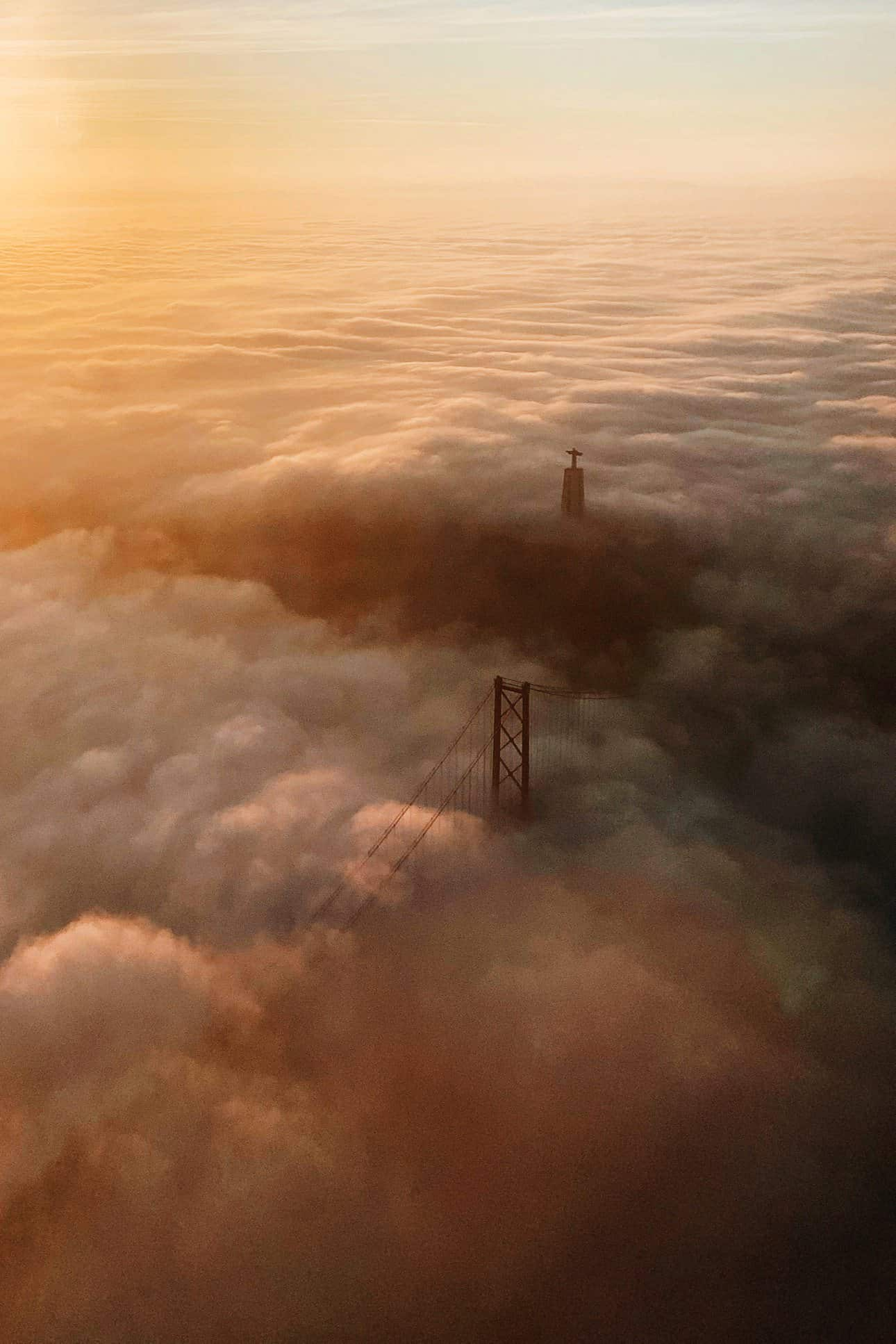 Looking on top of a bridge which is surrounded by clouds