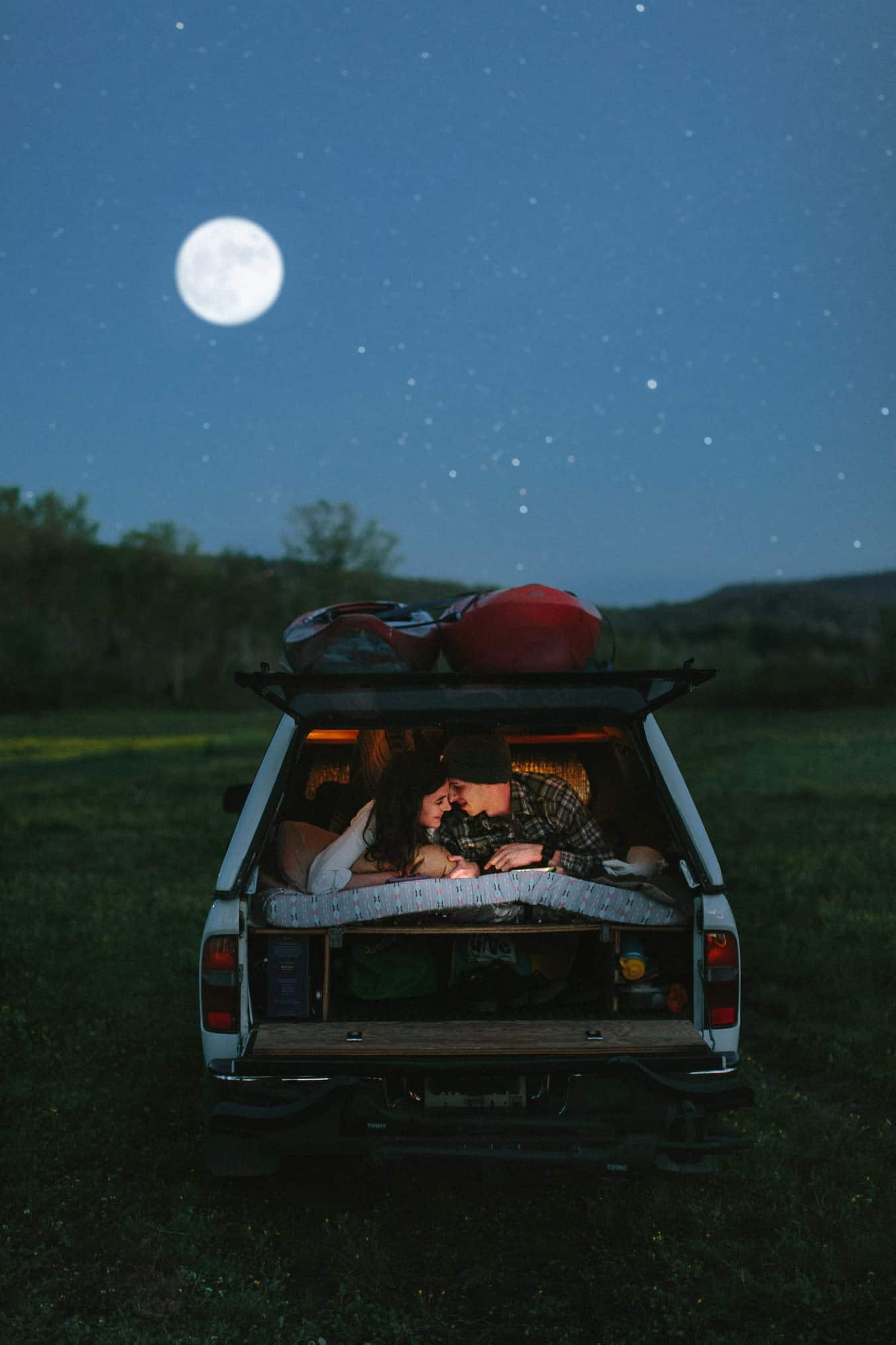 Two lovers laying in the back of their car while the moon is shining