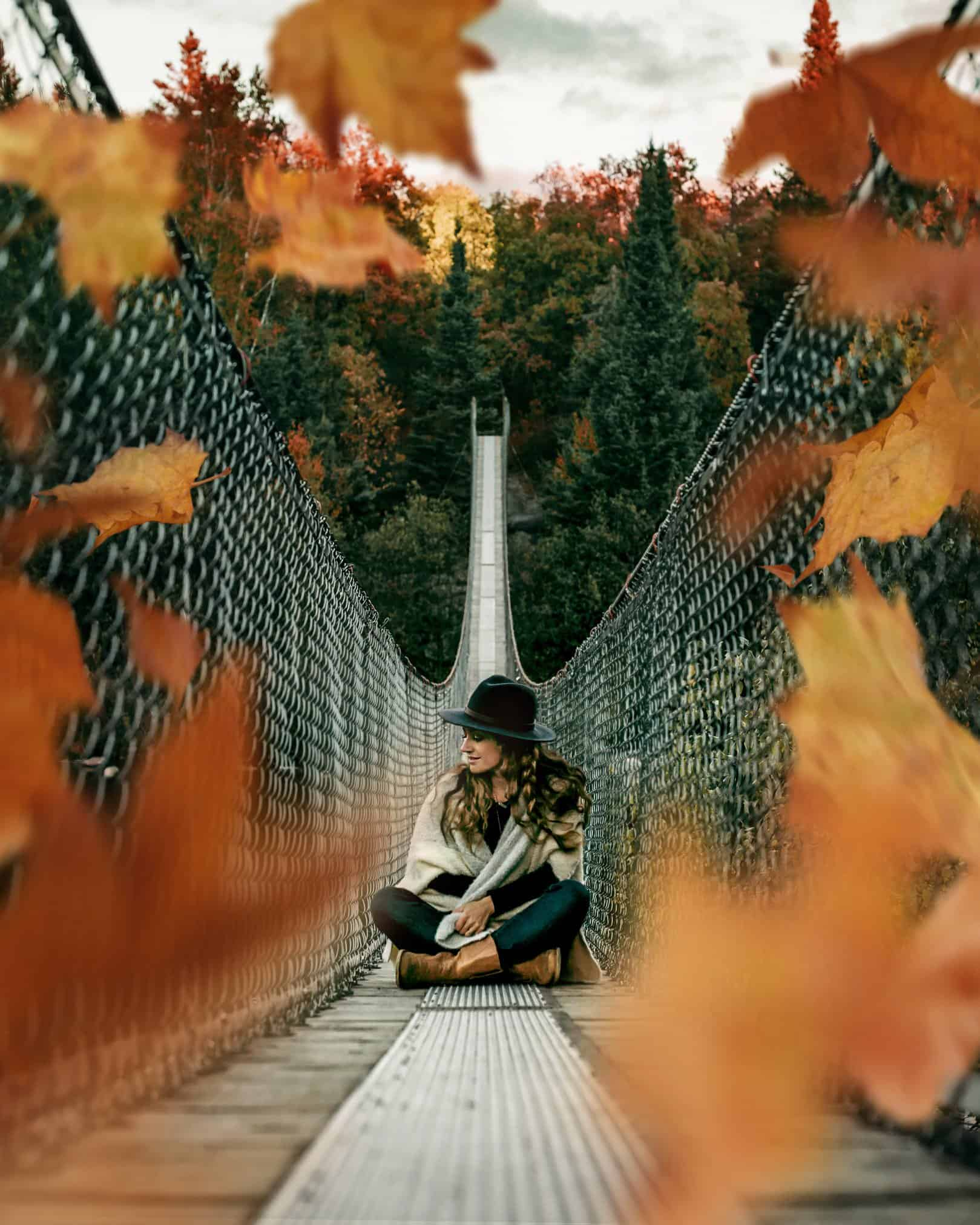The leaves are falling and a woman is sitting on a suspension bridge