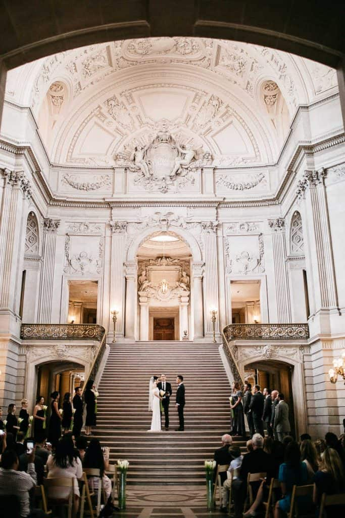 bride and groom standing in front of each other on the stairs inside the San Francisco city hall