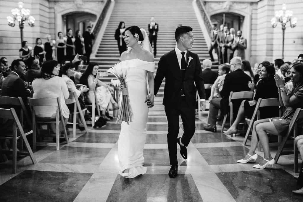 Wedding couple making their exit inside the city hall in SF