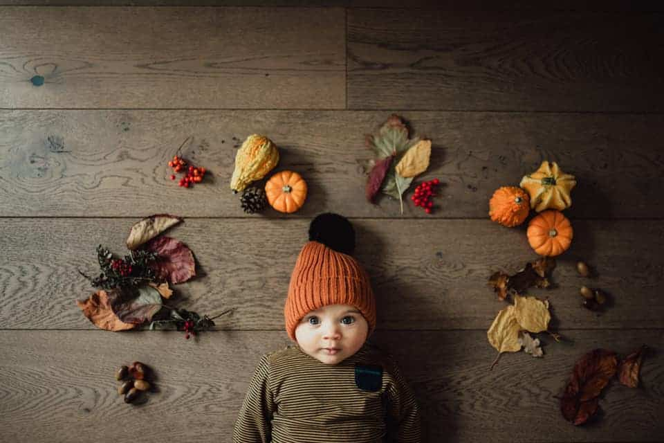 A kid laying on the floor looking up into the camera surrounded by autumn themed items