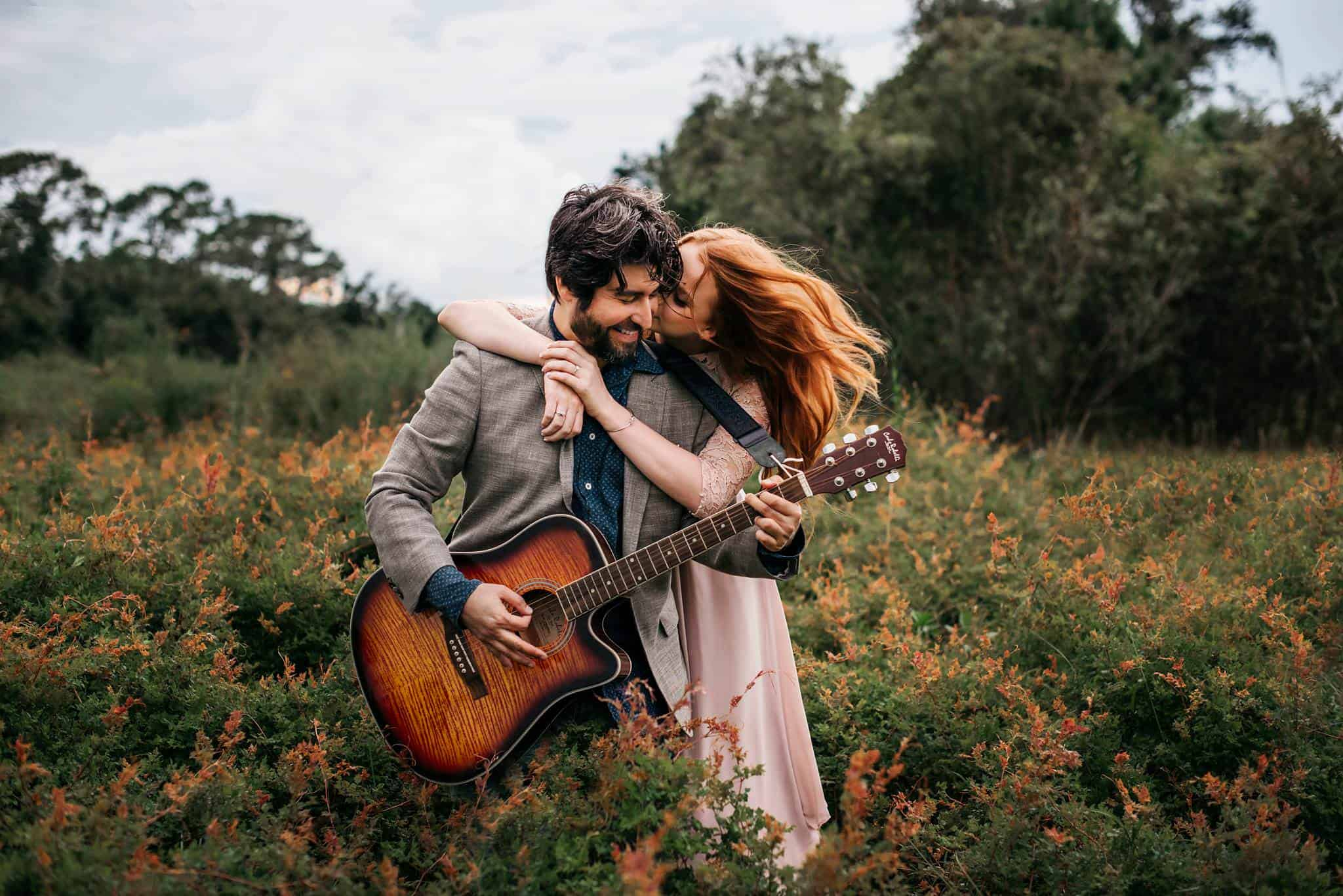 A girl holding her man while he is playing a guitar