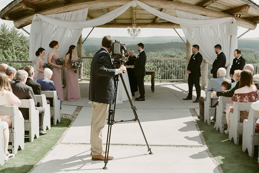 A man standing in the middle of the aisle is filming the bride and groom.