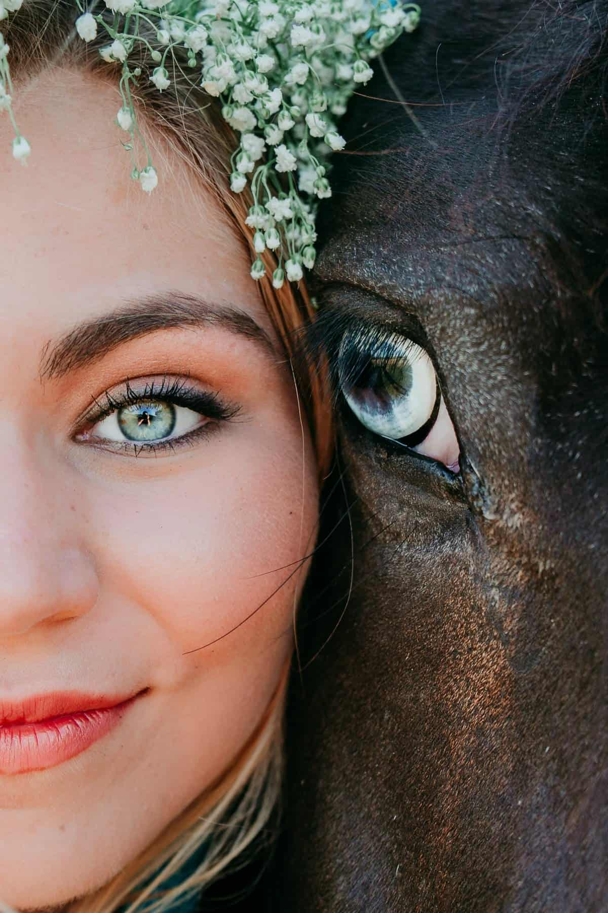 A close up of half of the face of a horse and a woman