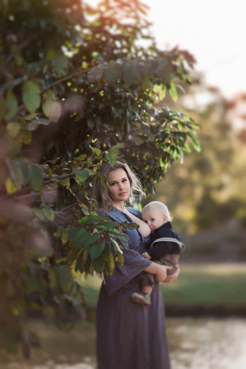 A woman breastfeeding her baby next to a tree