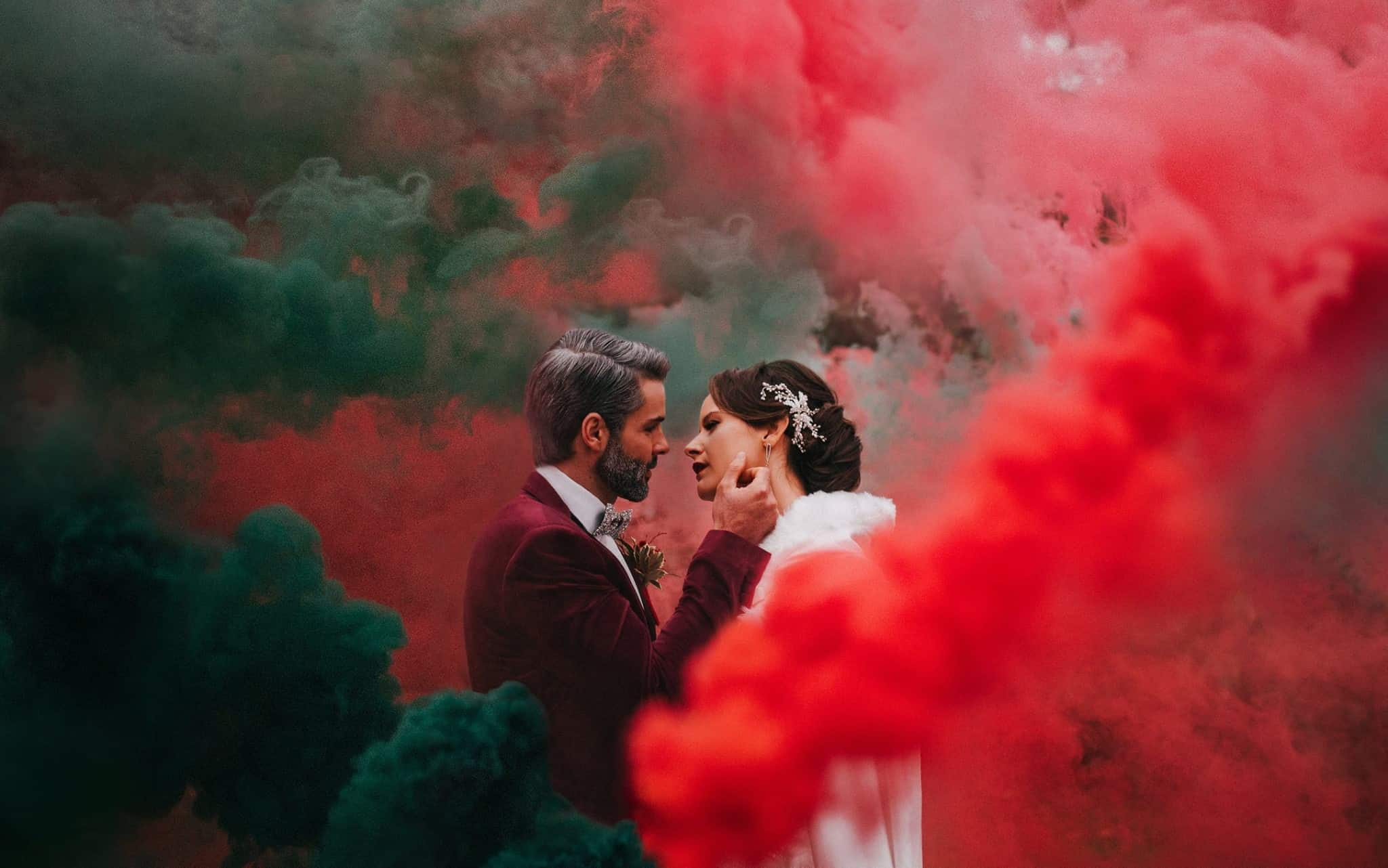 Wedding couple surrounded by a smoke grenade