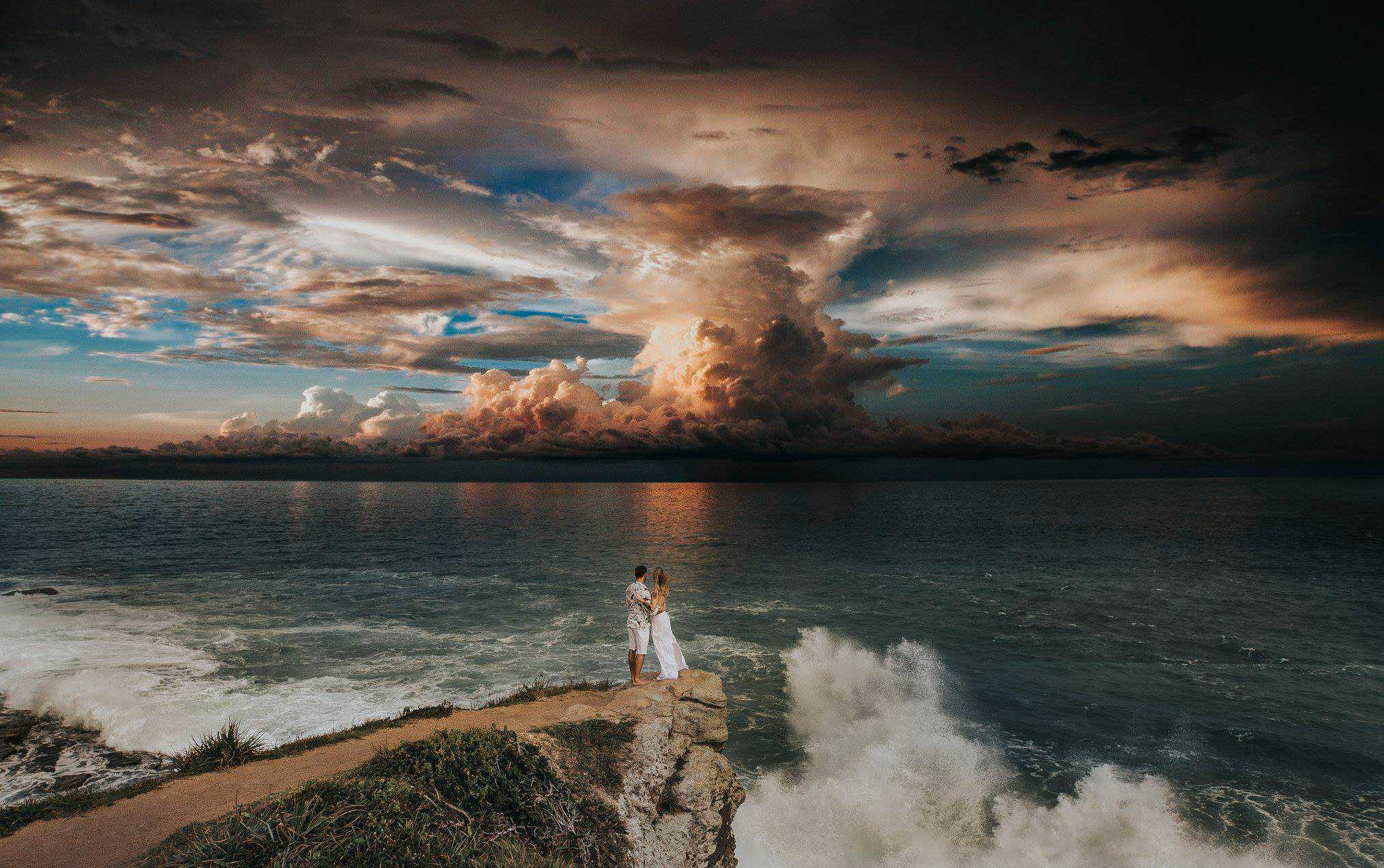 Man and a Woman standing on a cliff watching a storm