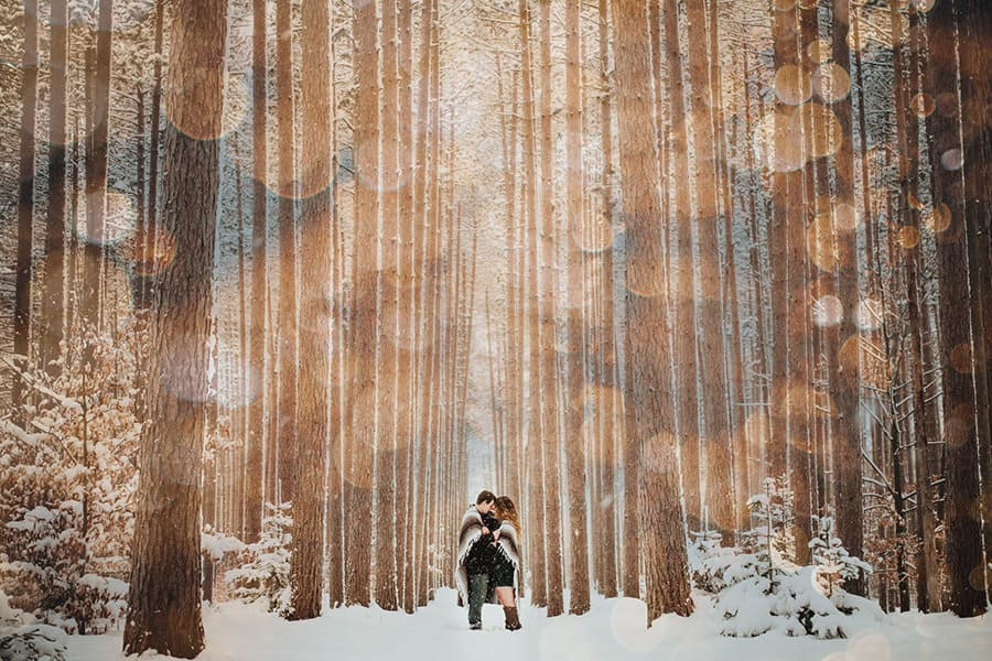 A couple standing in a snowy forest