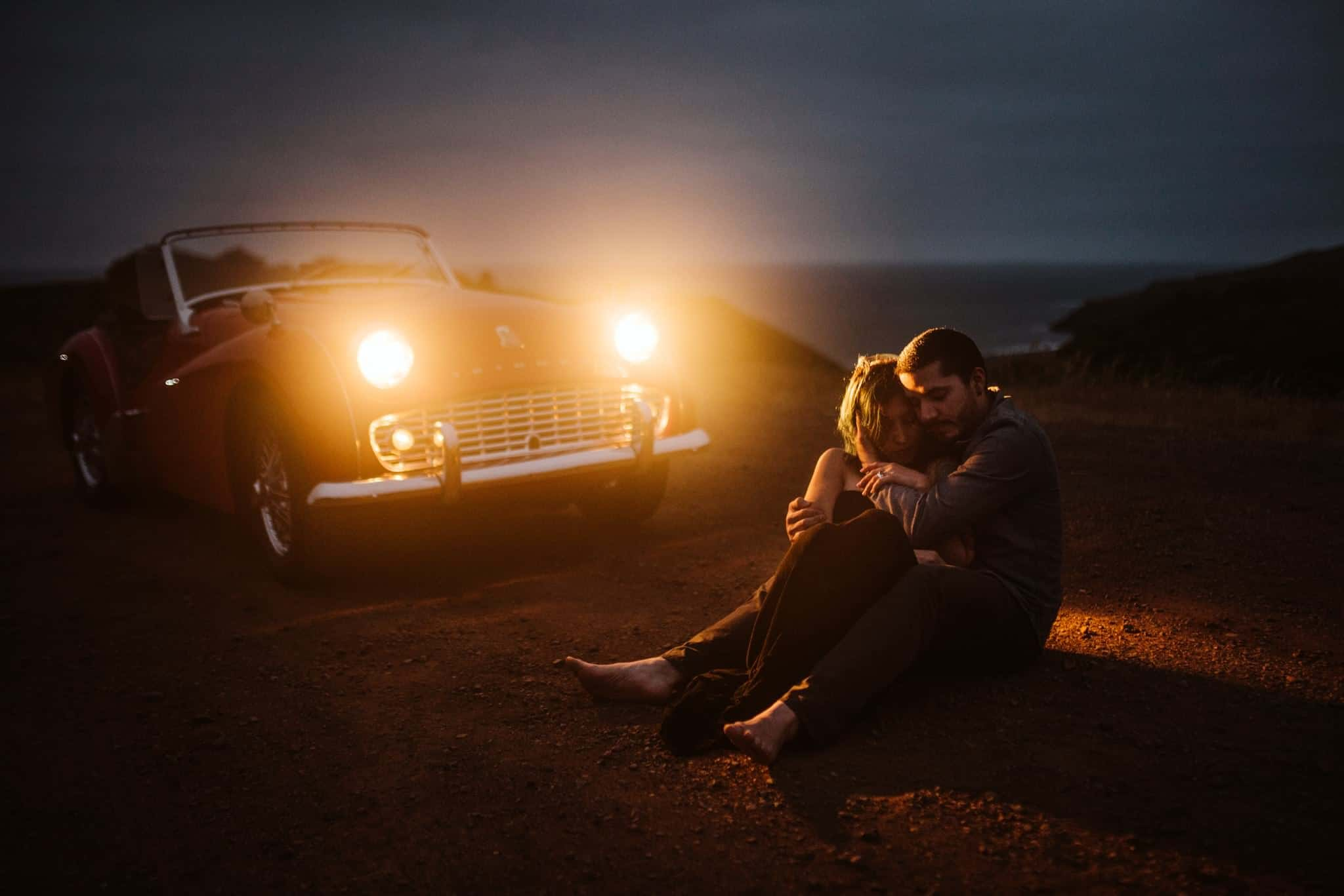 Two lovers sitting on the ground at night lit up by a car