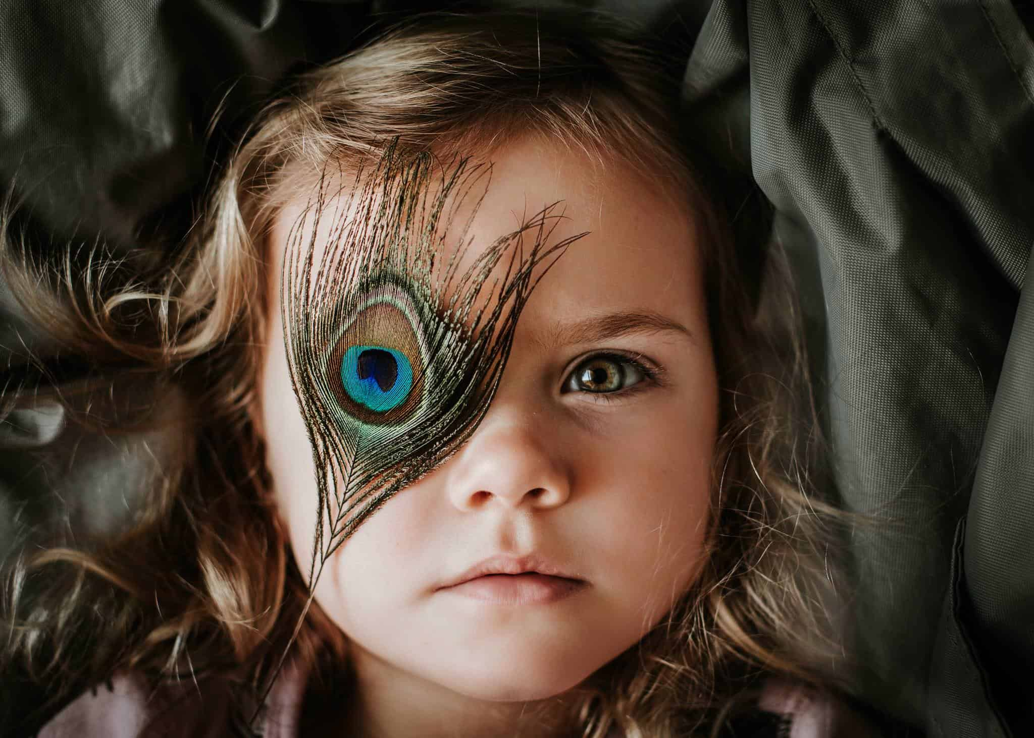 Kids Portrait of a young girl with a peacock feather in fron of her eye