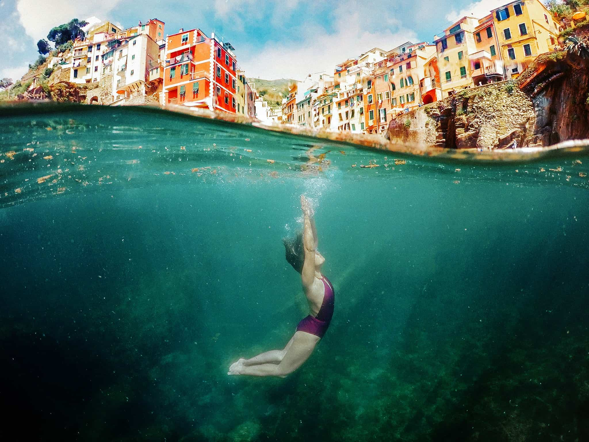 A woman swims underwater in front of buildings