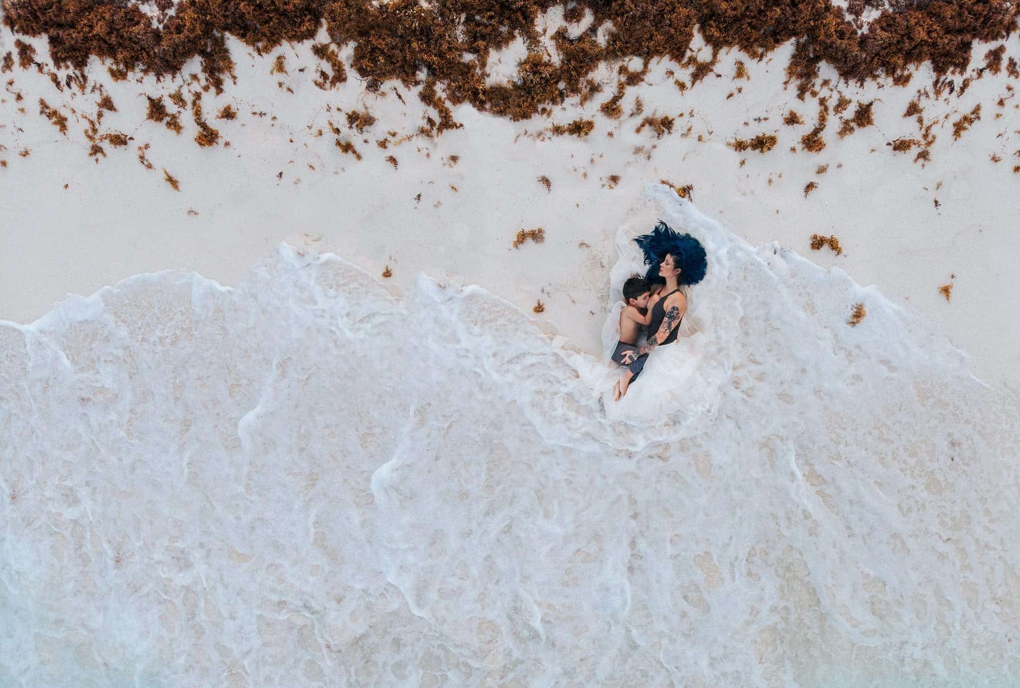 Drone photo of a mother breastfeeding in the ocean