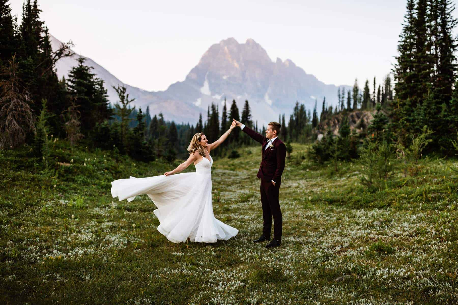 Bride and groom are dancing in the middle of nature with a stunning mountain in the background