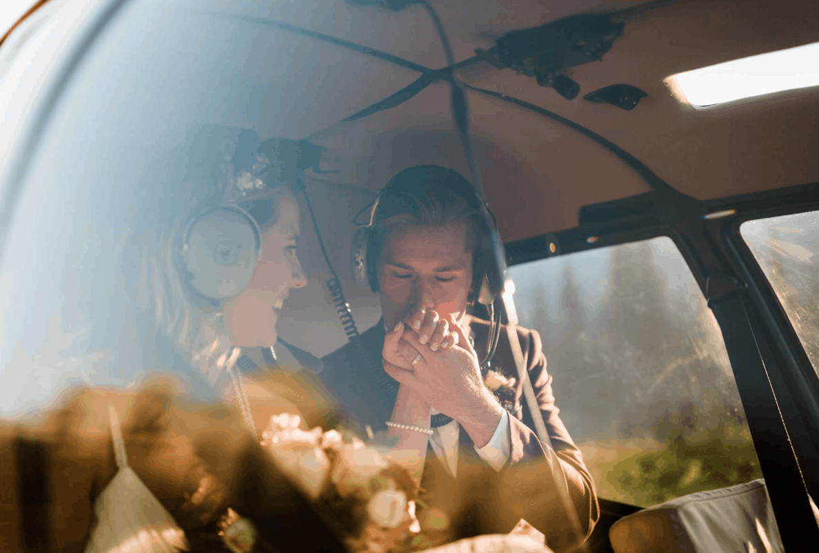 The groom kisses the hand of his bride while they are sitting in a helicopter