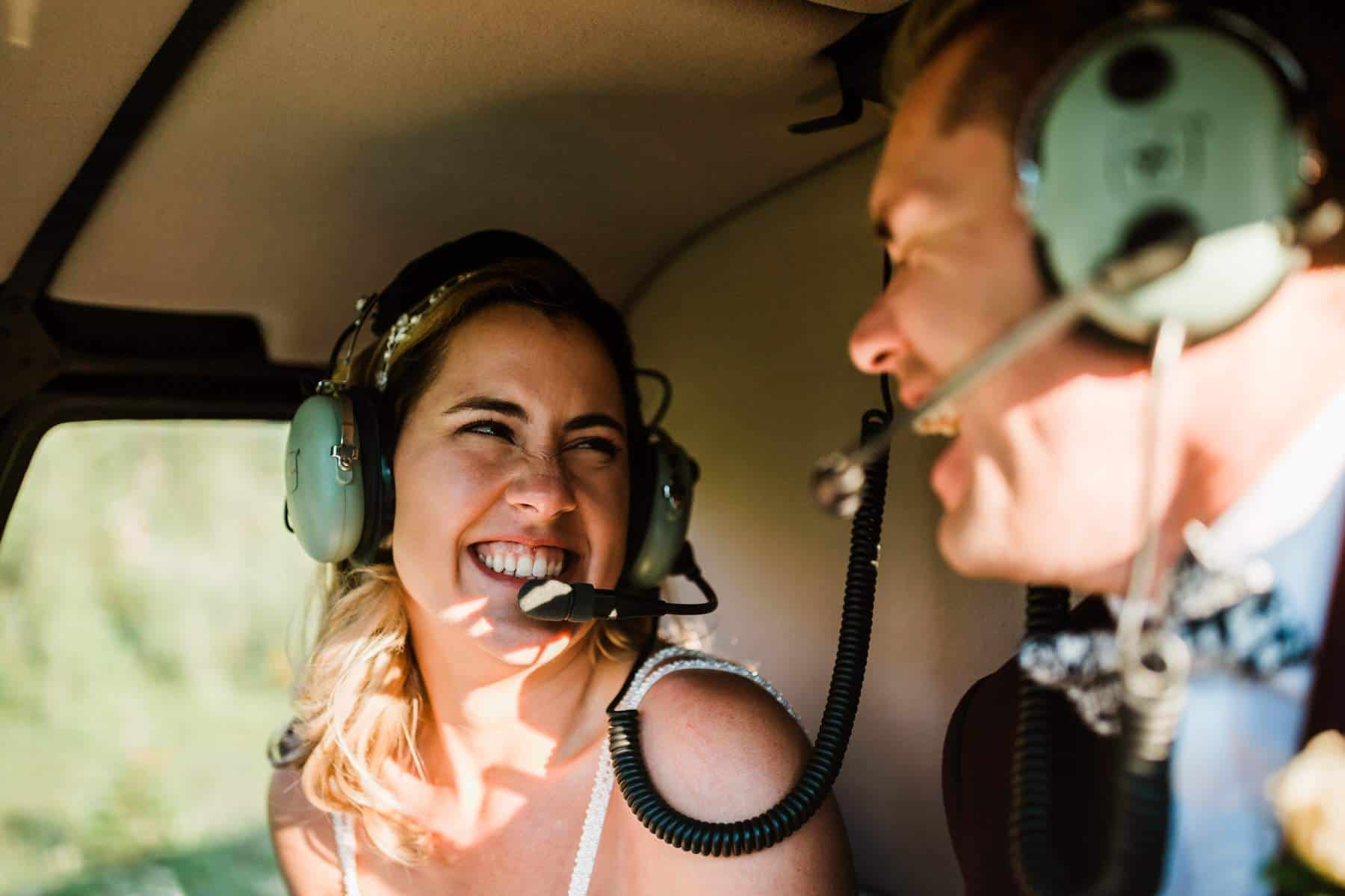 Bride and groom laugh and wear headphones in the helicopter