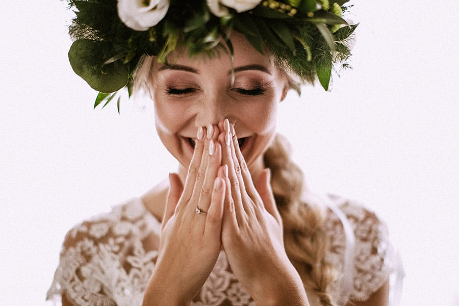 A bride holds her hands together in front of her nose and laughs