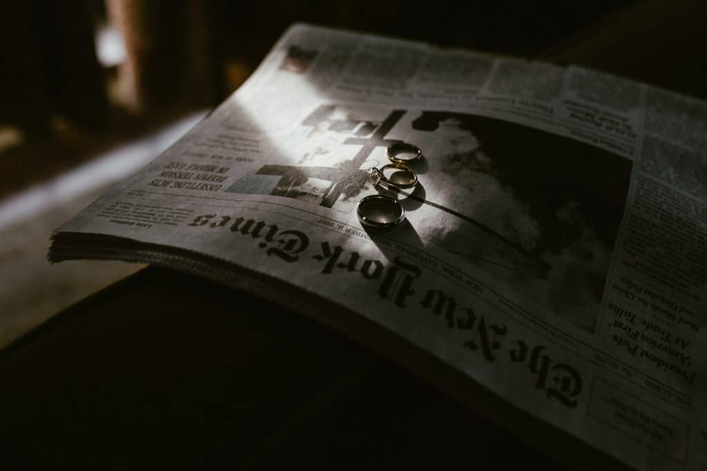 The rings of the bride and groom has been placed on a new york times newspaper