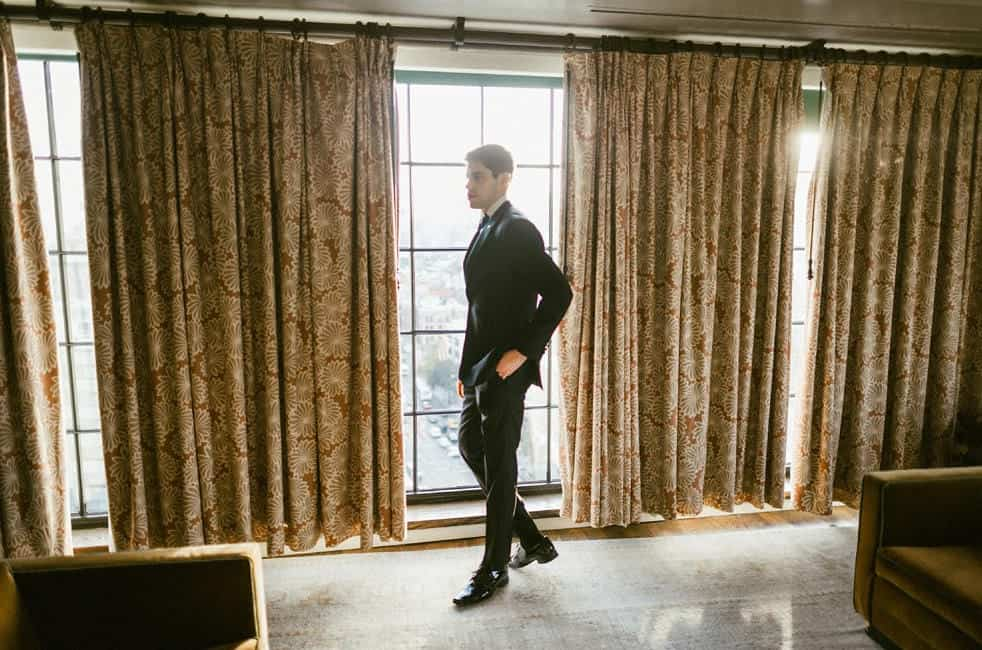 the groom waits for his bride and walks up and down in his hotel room