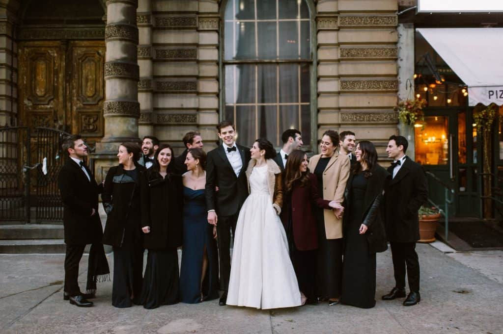 A group photo of the newlyweds and a part of their wedding guests on the streets of Brooklyn