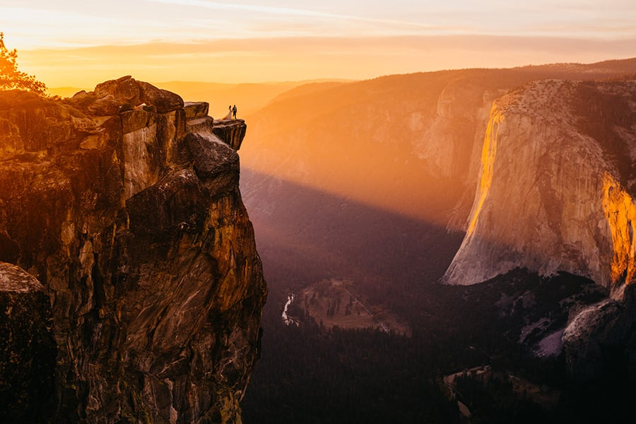 A wedding couple stands at the edge of a mountain while the sun is shining
