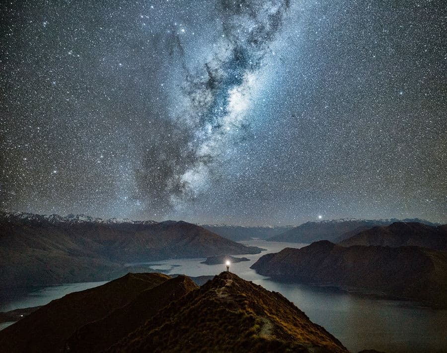 The sky is full of stars and a person stands on top of mountain with a flashlight