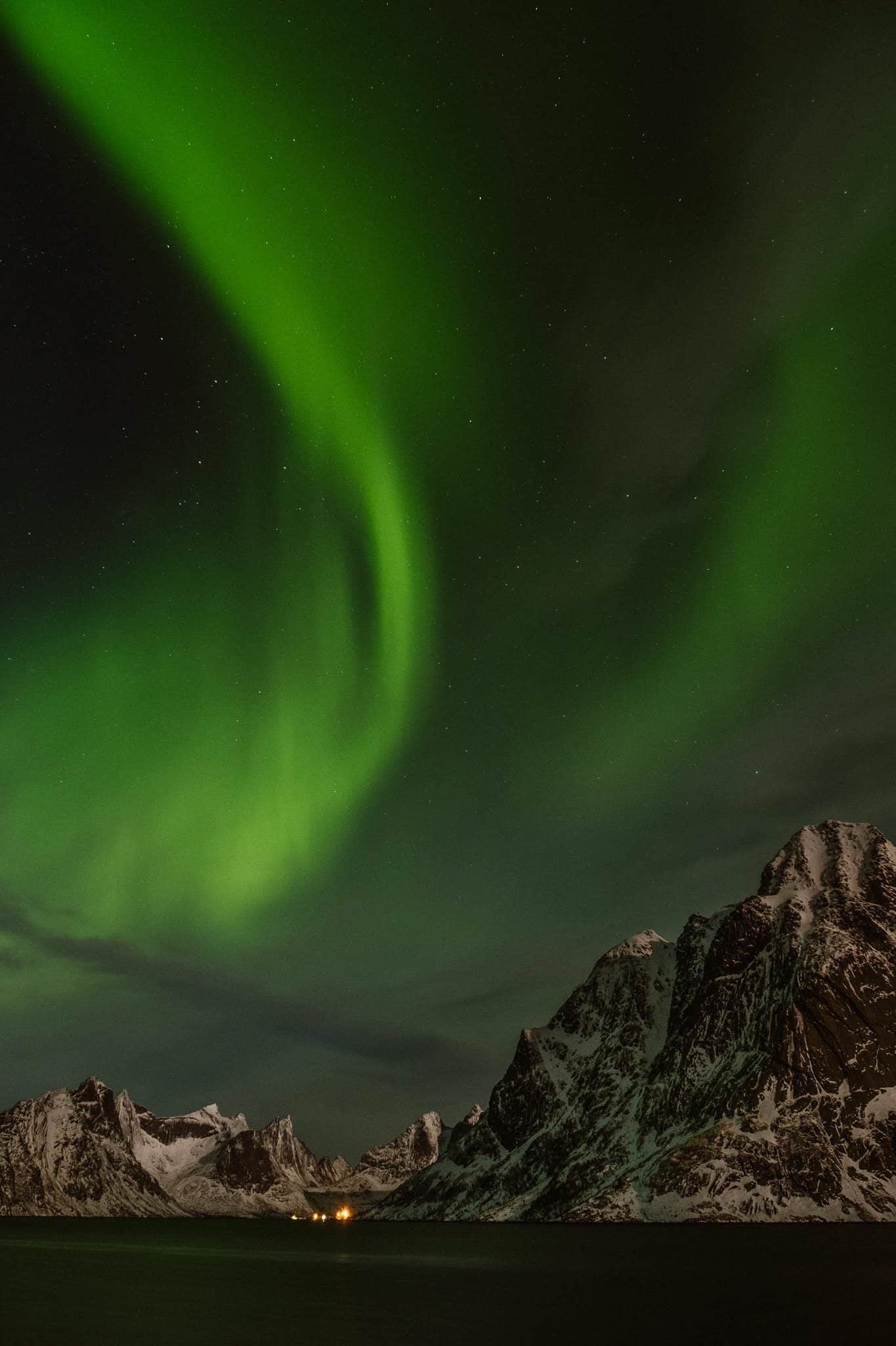 Observing the northern lights which are over a mountain.