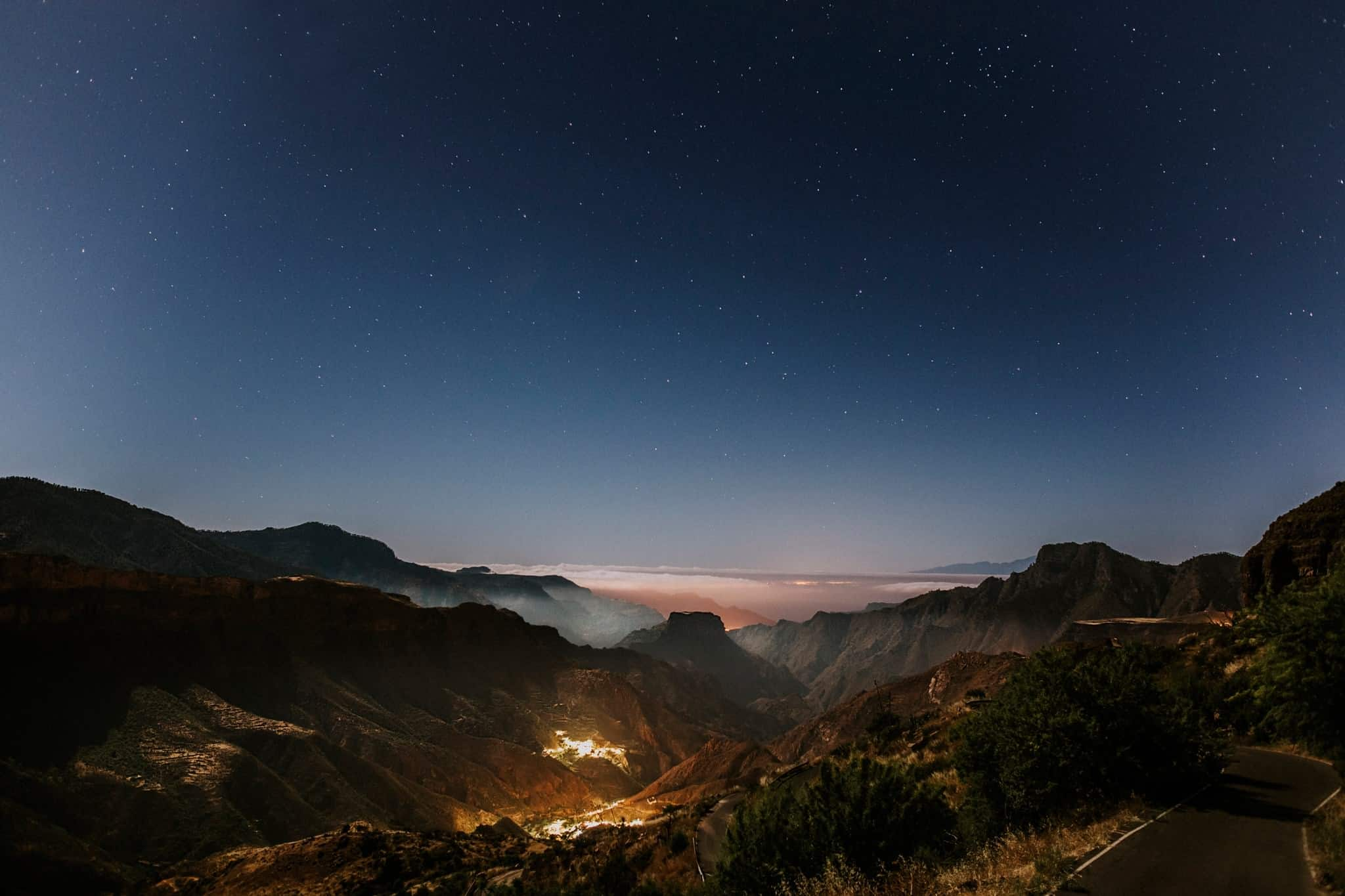 Looking down at night on a city which is located in a valley between mountains