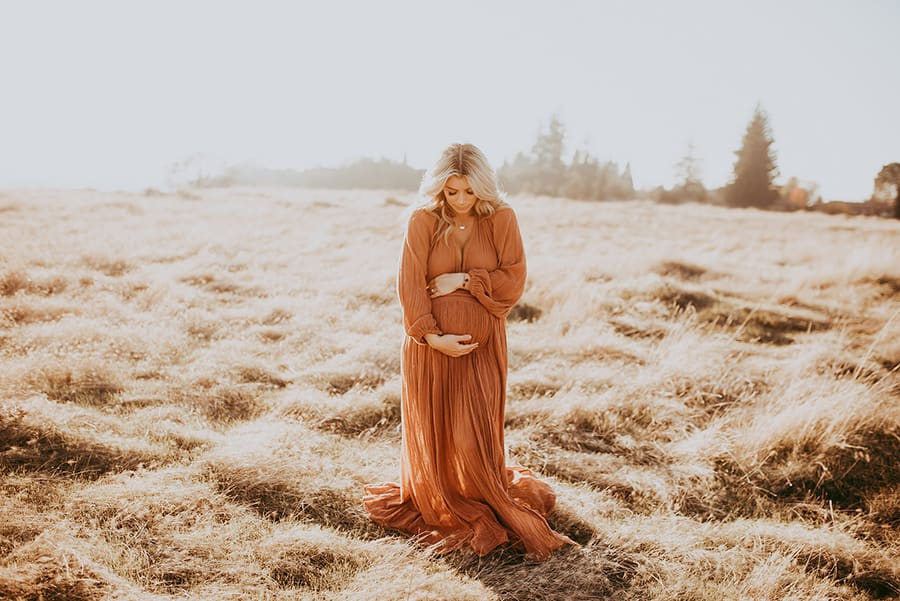 A woman who is pregnant stands on a field, looks on her belly and holds it with her hands