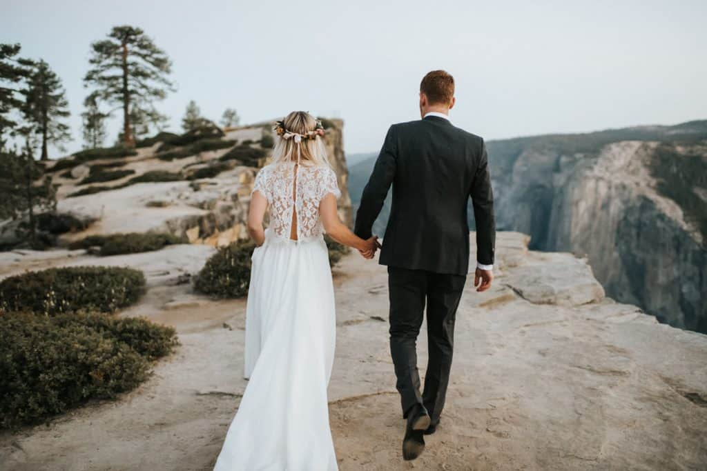 a bridal couple walking to taft point for a wedding