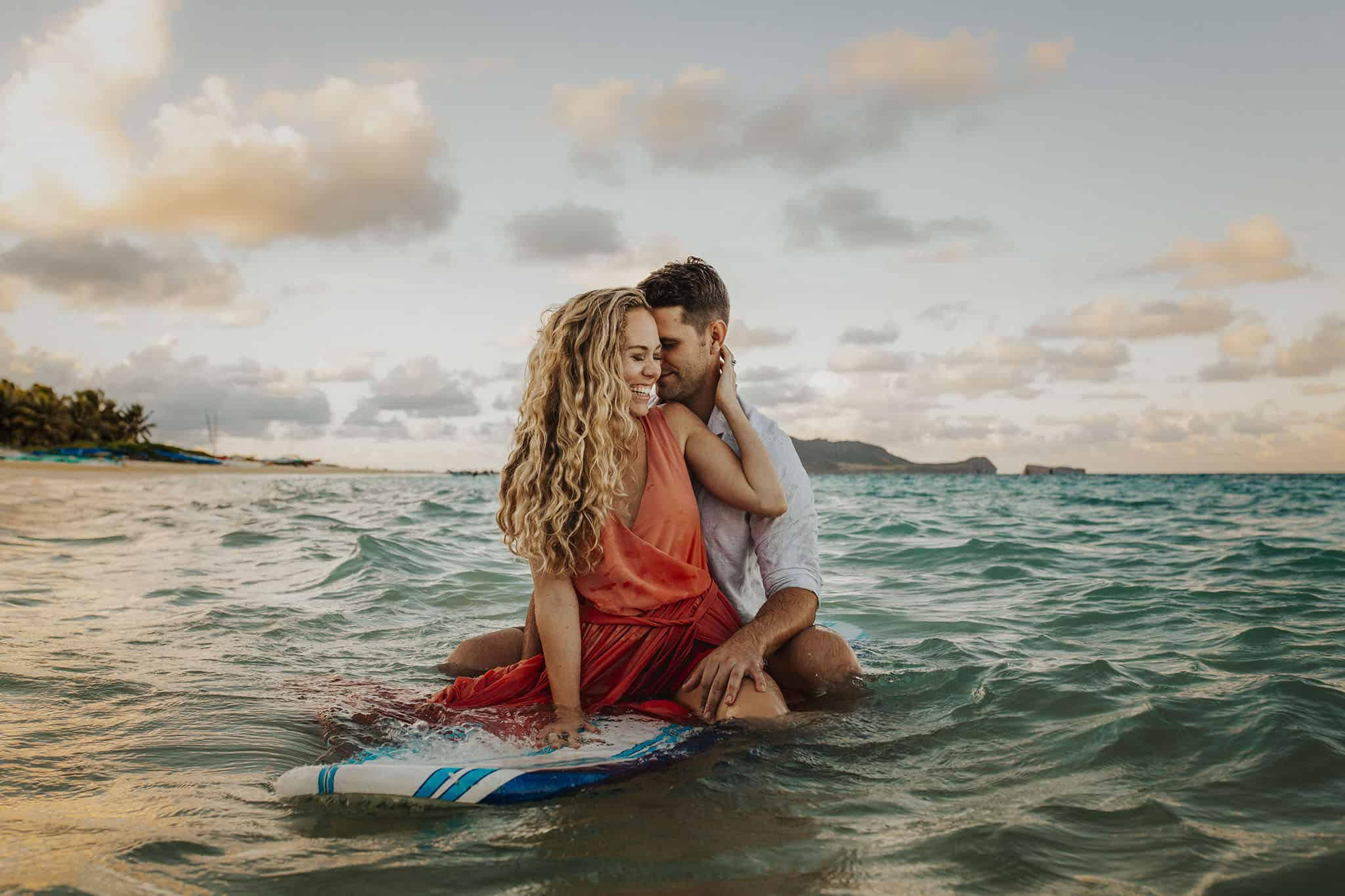 Couple Poses on a surfboard in the ocean