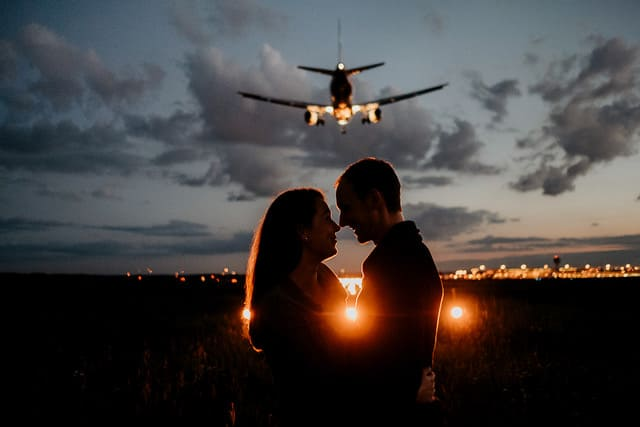 Couple Poses in front of a landing plane