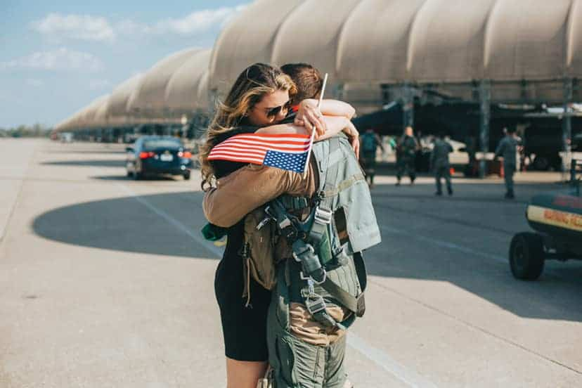 A woman is hugging her soldier that just came back from duty