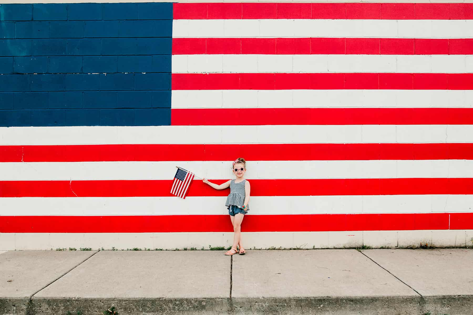 Small girls standing in front of a large US Flag printed wall on Independence Day