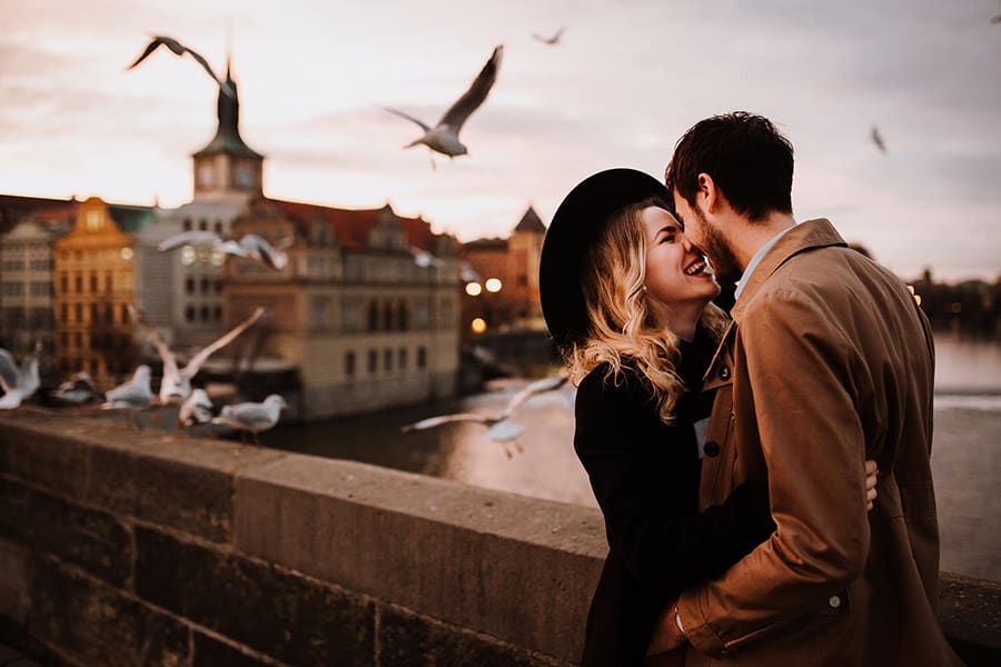 Couple Poses kissing on a bridge while seagulls fly over them