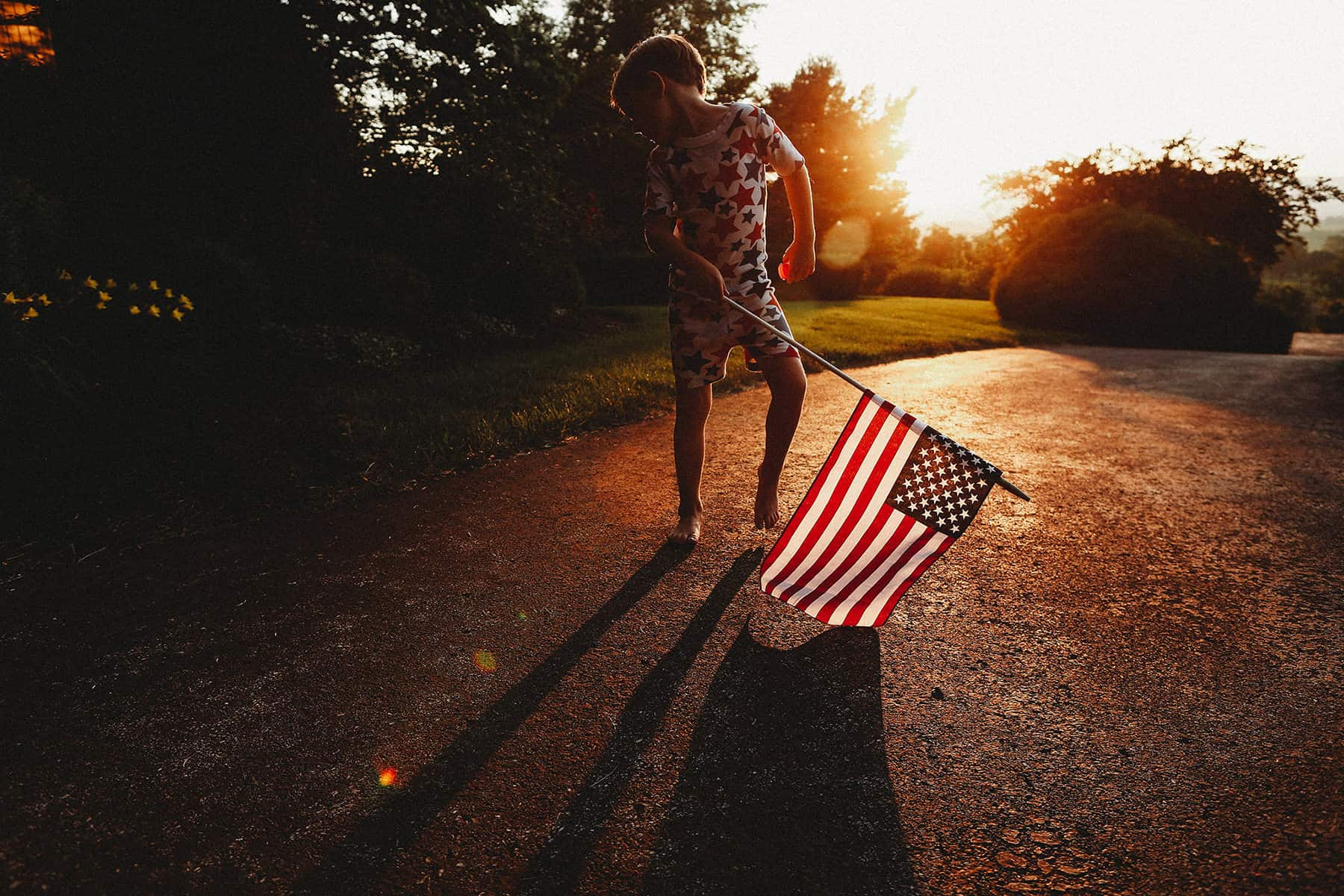 a 4th of July photo with a kid dancing at sunset with the US flag