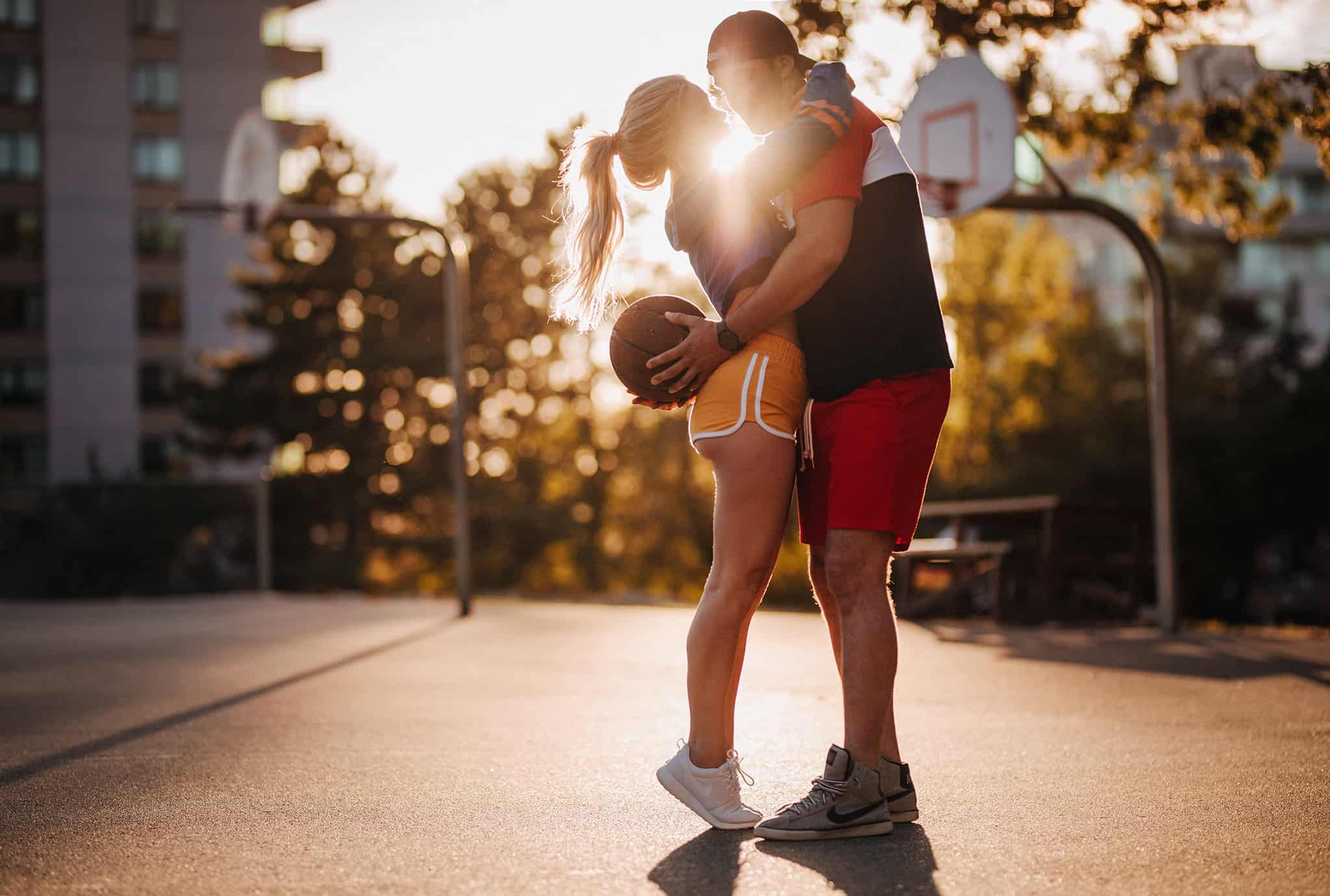 Couple Poses kissing on a basketball court