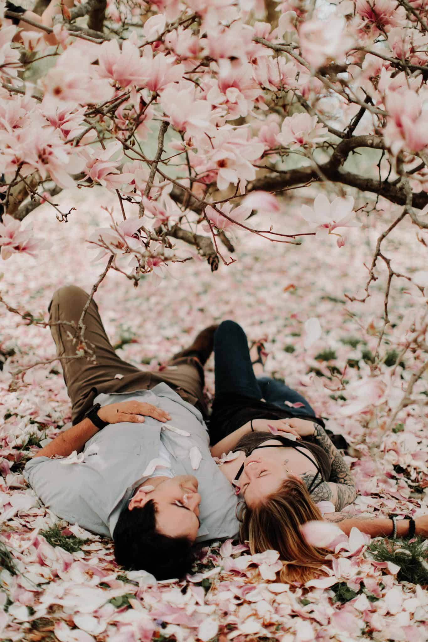 Couple Poses lying in a bed of flower petals