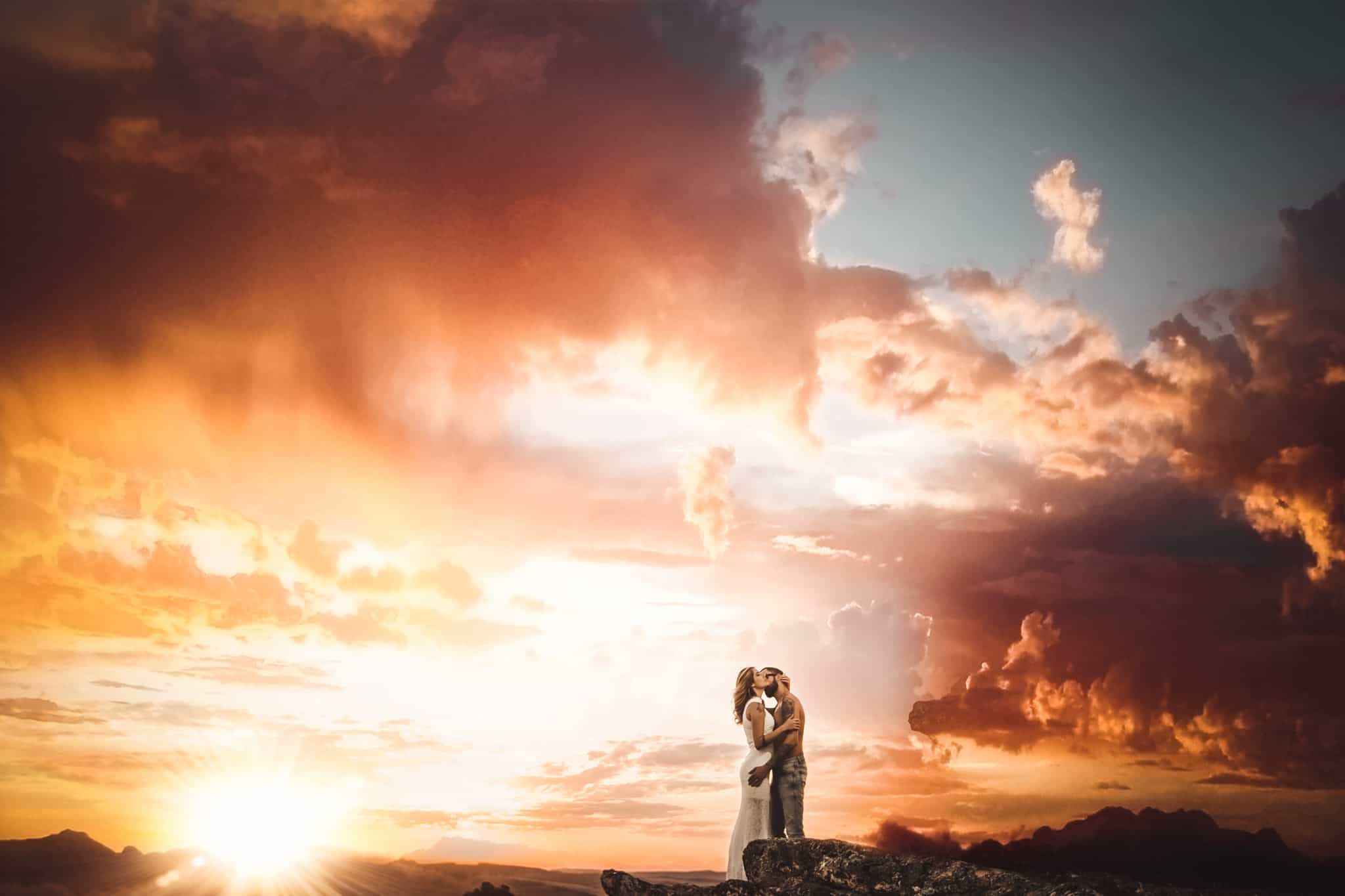 Couple Poses in front of an epic sky