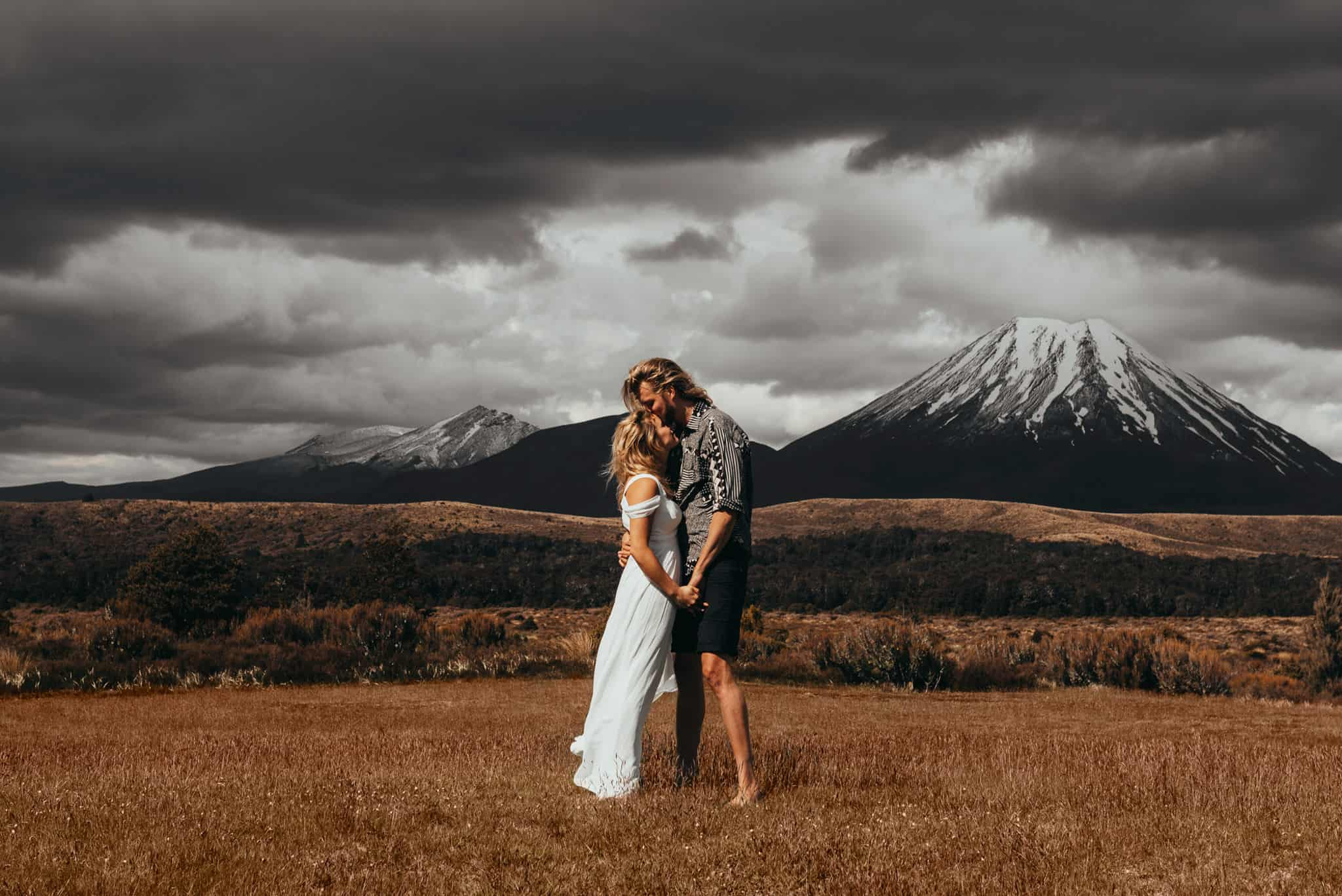 Couple Poses in front of a mountain