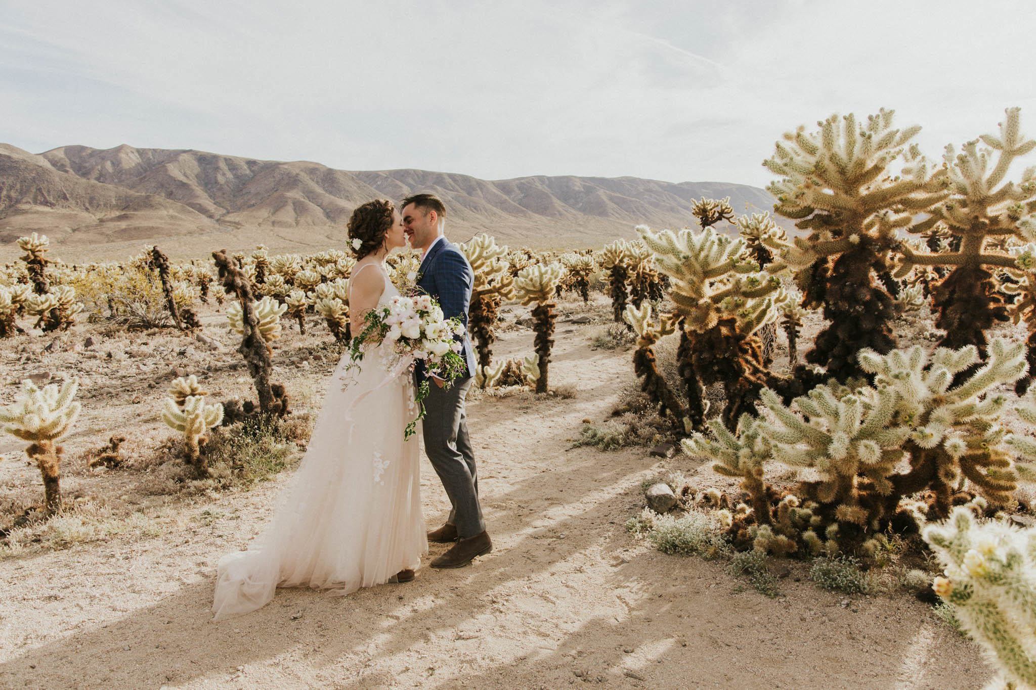 A couple is photographed by a wedding photographer California and is kissing each other.